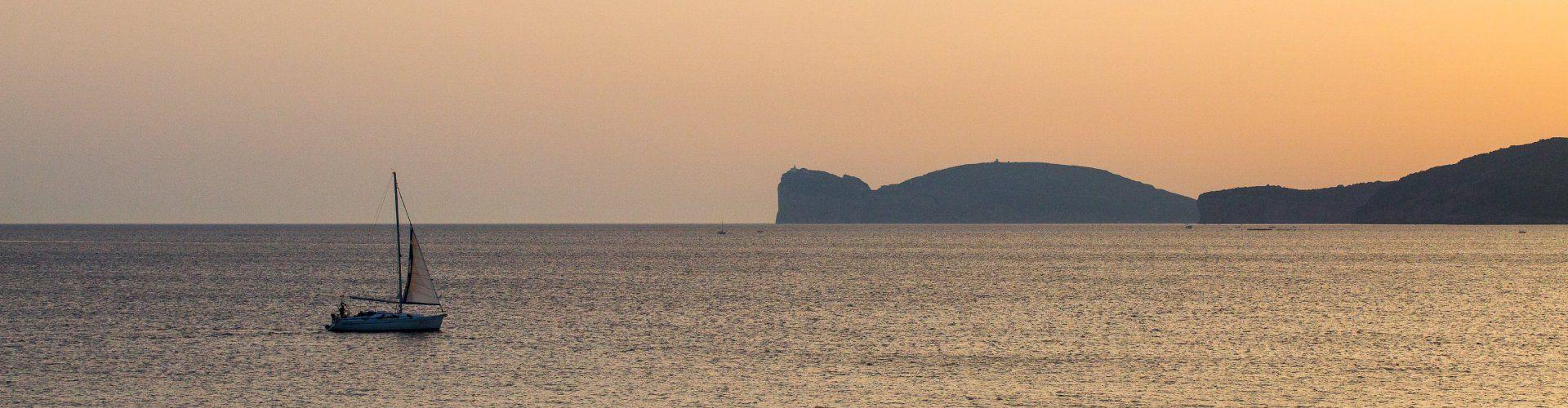 Il mare di Alghero al tramonto con una barca vela e Capo Caccia all´orizzonte