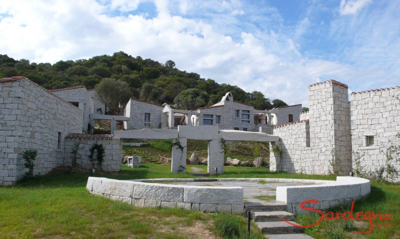 Un sentiero che passa per archi in granito e piazzette porta dalle case alla piscina in comune