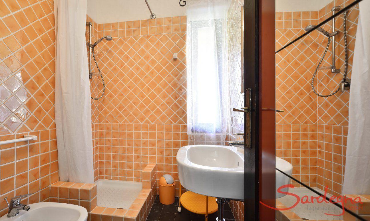Bagno con piastrelle arancione con doccia di  Villa Serena, Costa Rei