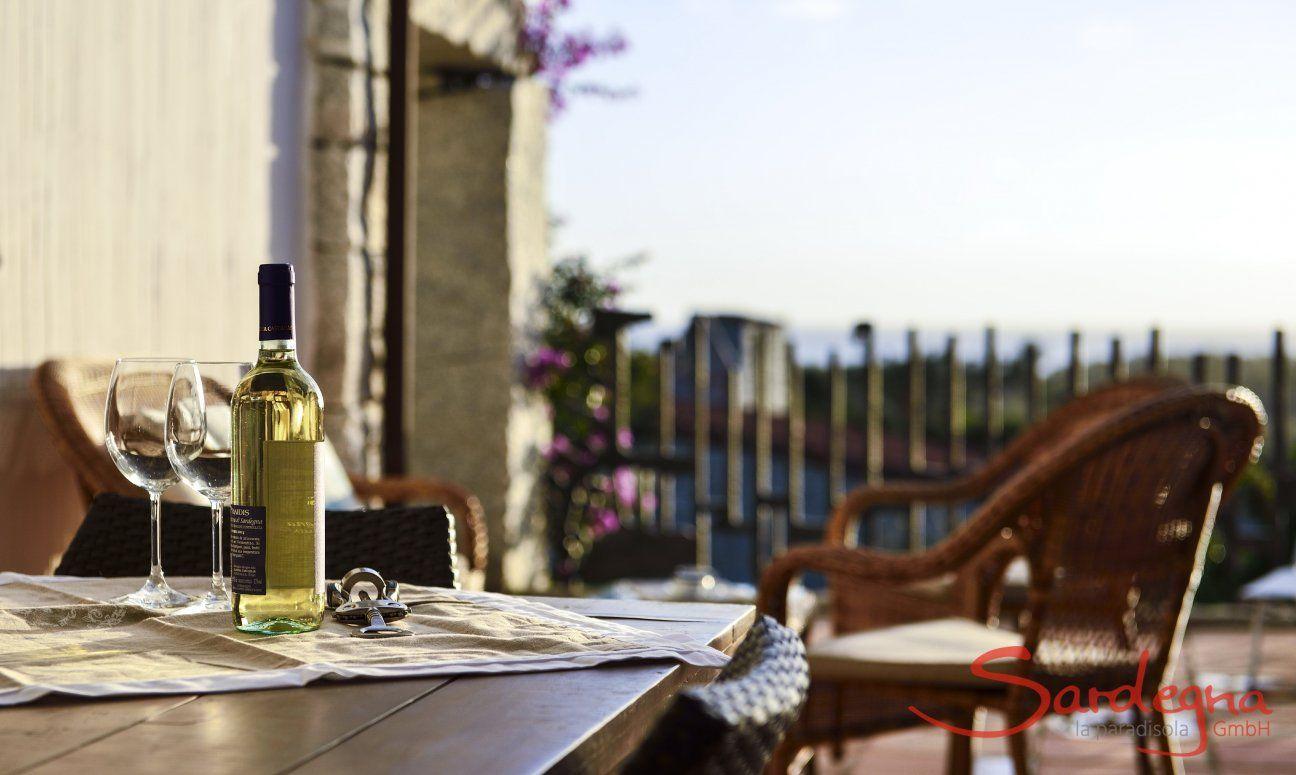 Bottiglia di vino bianco con due bicchieri sulla veranda di  Li Conchi 7 con vista mare