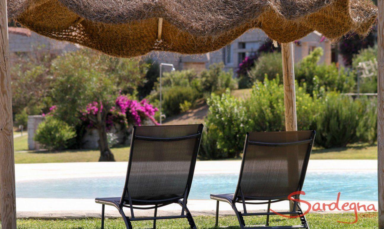Lettini da sole sotto un ombrellone a fianco alla piscina di Li Conchi
