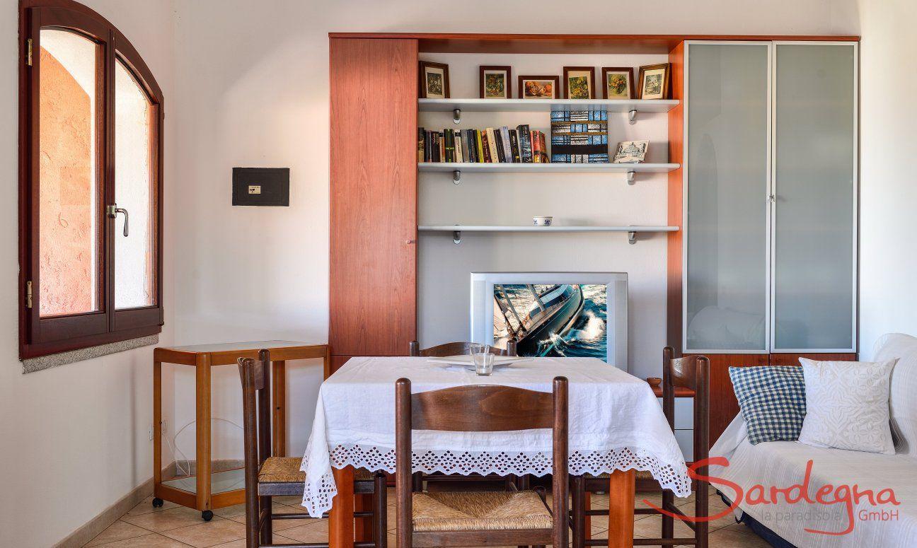 Sala al primo piano con tavolo, divano e libreria