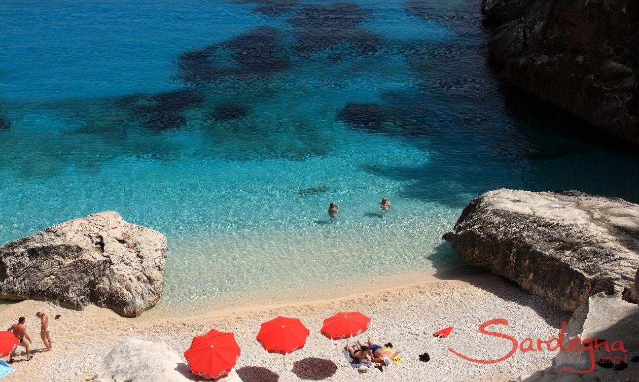Tre ombrelloni rossi sulla spiaggia paradisiaca di Cala Goloritze