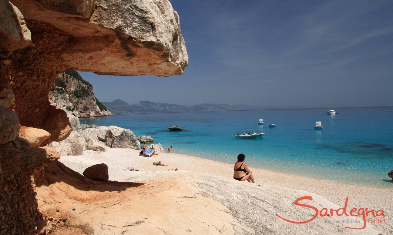 Donna seduta sulla spiaggia davanti alle rocce di Cala Luna guardando il mare e i gommoni sul mare