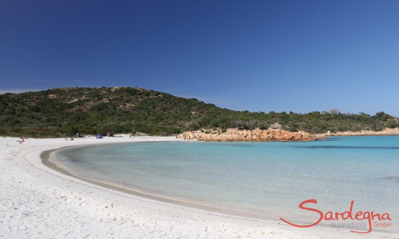 Spiaggia Romazzino fatto di sabbia bianca a forma di mezza luna, alla fine rocce giallie e una collina coperta di macchia verde