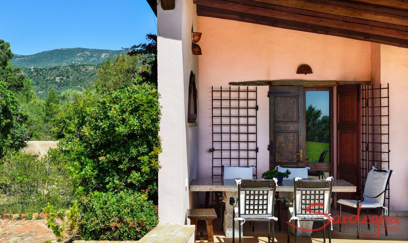 Veranda ombreggiata con tavolo in granito e vista nel verde d'intorno