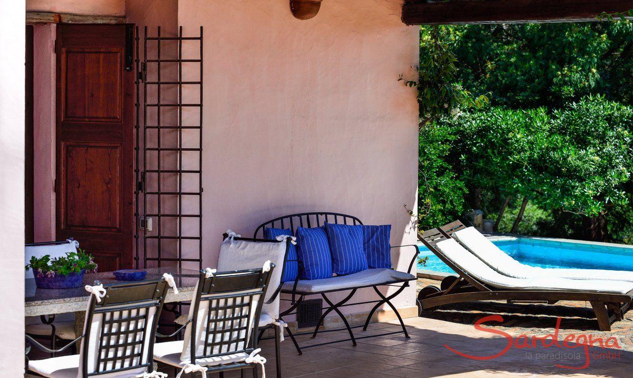 Veranda con tavolo, panca e lettini a bordo piscina