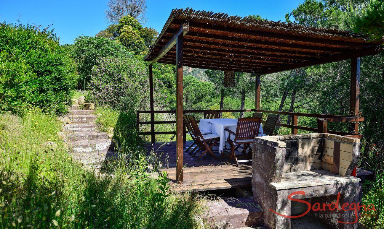 Veranda coperta in legno con tavolo, sedie e barbecue murato per grigliate