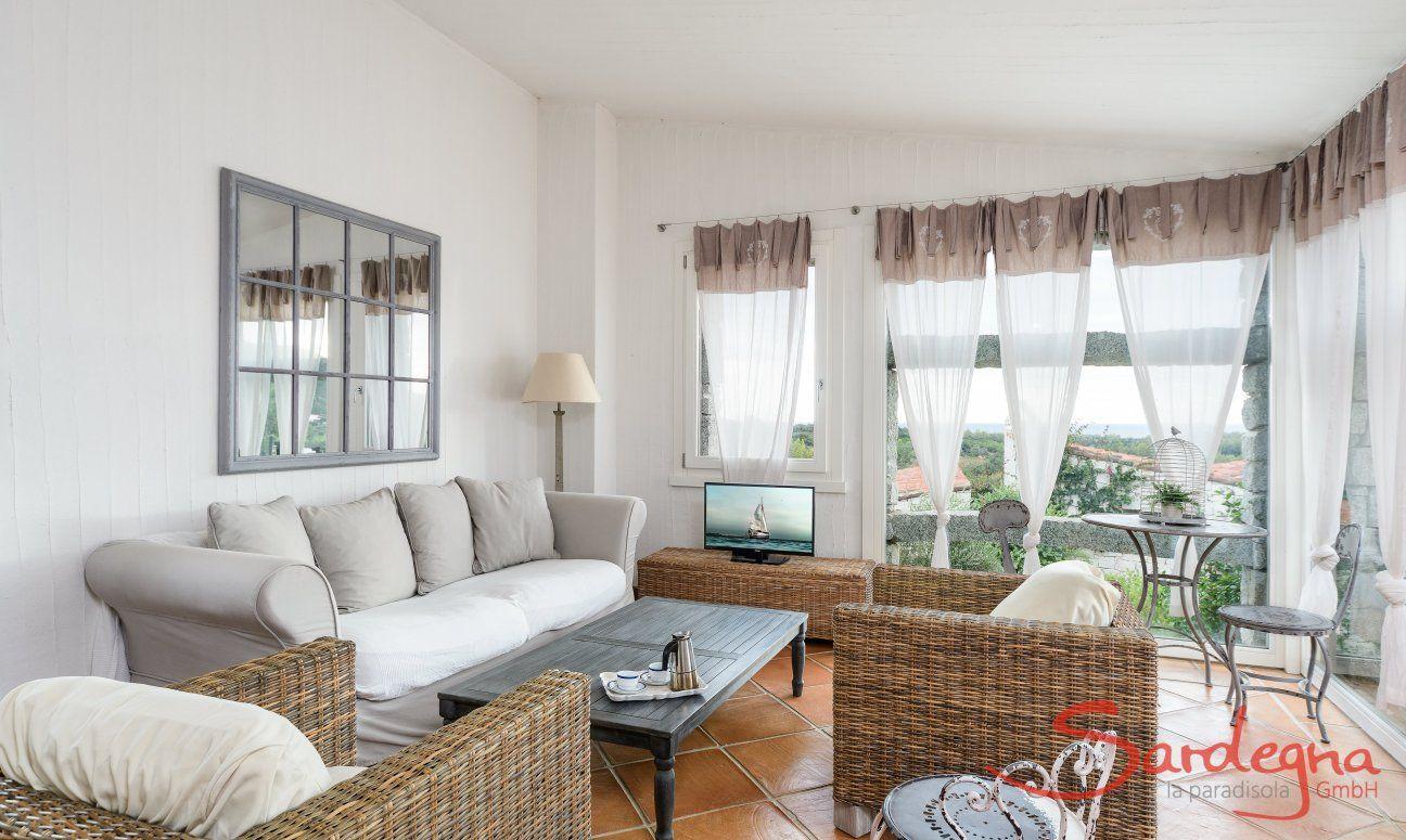 Salotto con divano e TV e grande finestra