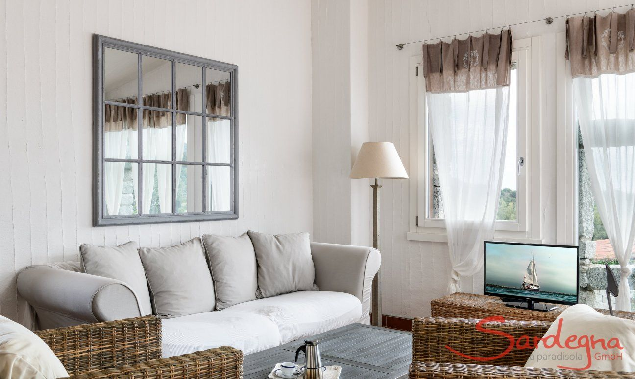 Angolo divano con divani in vimini, tavolino e TV