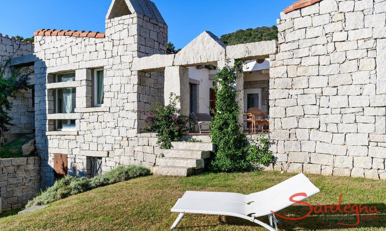 Facciata in granito della casa con scala che porta sulla veranda