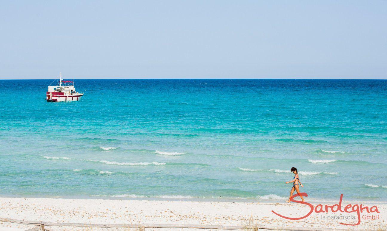 Una donna cammina sulla battiggia bianca della spiaggia La cinta davanti al mare celeste con una barca bianca e rossa