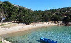Peschereggio tradizionale sospeso nell'acqua trasparente di Cala Moresca, Golfo Aranci