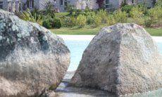 Piscina Li Conchi con grandi graniti e le case sullo sfondo