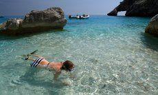 Giovane ragazza con maschera e pinne nelle acque trasparenti di Cala Goloritze