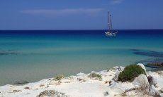 Spiaggia con mare turchese e barca a vela