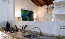 Piano di lavoro della cucina con lavello, fornelli a gas, forno e apertura alla sala