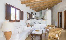 Angolo divano e cucina aperta di  Villa Fiori 2 a Is Molas