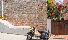 Una vespa è parcheggiata davant a un muro in pietre e un oleandro in fiore a Santa Teresa di Gallura