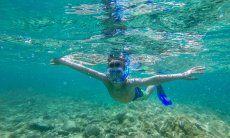 Bambino che fa snorkelling nel mare di Olbia