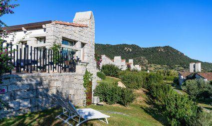 Casa in granito e giardino con lettini da sole